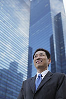 Mature man in a business suit, smiling in front of a building - Alex Mares-Manton