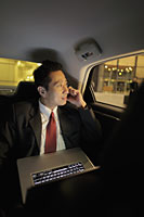 Mature man sitting in back seat of the car with a laptop and phone - Alex Mares-Manton