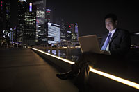 Mature man working on his laptop at night, buildings in background - Alex Mares-Manton
