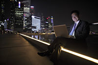Mature man working on a laptop at night, buildings as background - Alex Mares-Manton