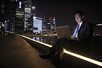 Mature man working on a laptop at night, lit buildings as background - Alex Mares-Manton