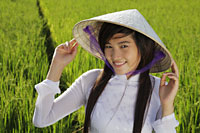 Young woman wearing traditional Vietnamese hat standing in rice paddy - Alex Mares-Manton