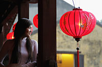 Young woman wearing traditional Vietnamese dress looking out from bridge with red lanterns. - Alex Mares-Manton