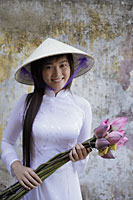 Young woman wearing traditional Vietnamese outfit holding lotus flowers - Alex Mares-Manton