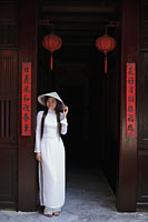 Young woman wearing traditional Vietnamese outfit standing in front of a temple, Vietnam - Alex Mares-Manton