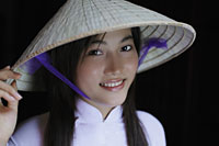 Young woman smiling, wearing Vietnamese hat - Alex Mares-Manton