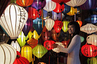 Young woman standing in front of colorful, hanging lanterns - Alex Mares-Manton