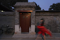 Woman walking in front of  Hutong, Beijing, China - Alex Mares-Manton