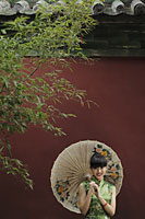 Young woman wearing Chinese traditional dress and holding an umbrella - Alex Mares-Manton