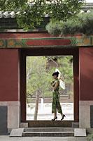Young woman walking through a doorway holding an umbrella - Alex Mares-Manton