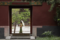 Young woman walking by Chinese doorway holding an umbrella - Alex Mares-Manton