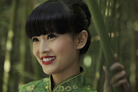 Head shot of young woman wearing a traditional Chinese dress and standing in front of bamboo trees. - Alex Mares-Manton