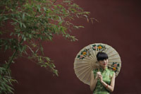 Young woman wearing a traditional Chinese dress holding an umbrella - Alex Mares-Manton
