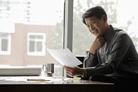 Mature man working near a window in an office - Alex Mares-Manton