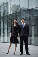 Young man and woman wearing suits, in front of a building - Alex Mares-Manton