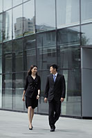 Man and woman wearing suits, walking in front of a building - Alex Mares-Manton