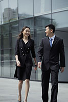 Young man and woman wearing suits walking in front of a building - Alex Mares-Manton