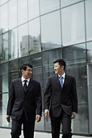 Businessmen walking together in front of a building - Alex Mares-Manton