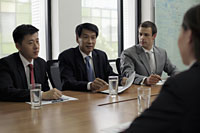 Businessmen having a meeting at conference table - Alex Mares-Manton