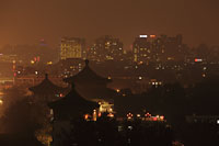 View of Beijing city scape at night with pagodas in foreground,China - Alex Mares-Manton