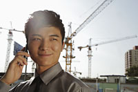 Young man with phone smiling, cranes in background - Alex Mares-Manton