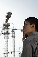 profile of young man holding phone standing in front of construction site - Alex Mares-Manton