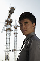 Young man standing in front of cranes - Alex Mares-Manton
