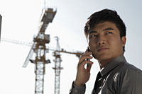 Young man talking on phone in front of construction site - Alex Mares-Manton