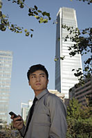 Young man holding phone standing in front of buildings, China - Alex Mares-Manton