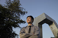 Young man standing in front of CCTV Building, Beijing, China - Alex Mares-Manton