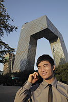 Young man talking on phone in front of CCTV Building - Alex Mares-Manton