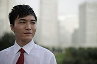 Head shot of man wearing a tie standing in front of buildings - Alex Mares-Manton
