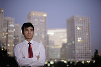 Young man standing in front of buildings in evening, China - Alex Mares-Manton