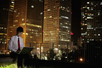 Young man working on laptop at night, with buildings in the background. Beijing, China - Alex Mares-Manton