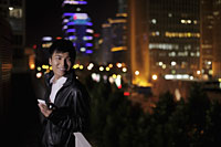 Young man holding a phone at night, Beijing, China - Alex Mares-Manton