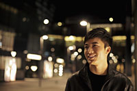 Young man smiling on the street at night - Alex Mares-Manton