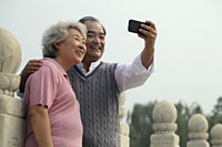Older couple smiling and taking a photo of each other - Alex Mares-Manton