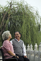 Older couple looking at each other and laughing in a park - Alex Mares-Manton