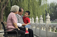 Grandparents talking with their grandson in a park - Alex Mares-Manton