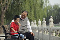 Grandfather with grandson in a park eating ice cream - Alex Mares-Manton