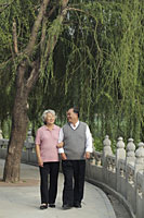 Older couple walking arm and arm in a park - Alex Mares-Manton