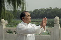 Older man doing Tai Chi in a park, Beijing, China - Alex Mares-Manton