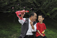 Grandfather and grandson playing with a kite - Alex Mares-Manton