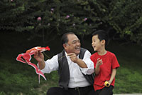 Grandfather and grandson playing with kite - Alex Mares-Manton