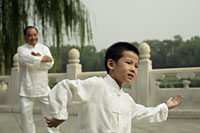 Older man watches young boy do Tai Chi, Beijing China - Alex Mares-Manton