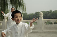 Young boy doing Tai Chi with older man in background - Alex Mares-Manton