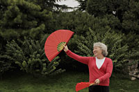 Older woman dancing with fan dance outdoors - Alex Mares-Manton