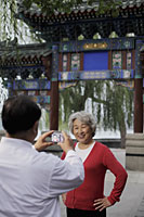Older couple taking photos in front of traditional Chinese gate - Alex Mares-Manton