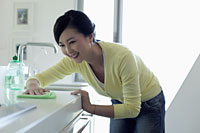Young woman wiping kitchen counter and smiling - Alex Mares-Manton