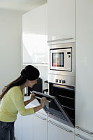 Young woman looking in oven - Alex Mares-Manton